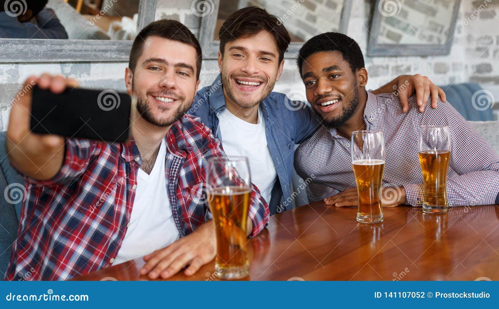 Vänner som gör selfie och ler och att vila på baren