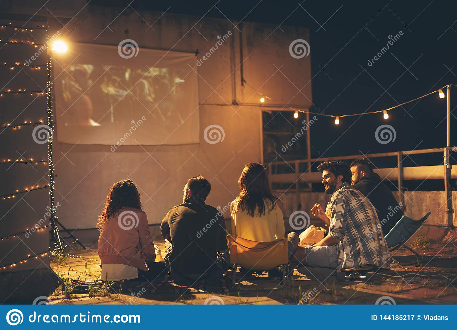 Vänner som håller ögonen på en film på en byggande takterrass