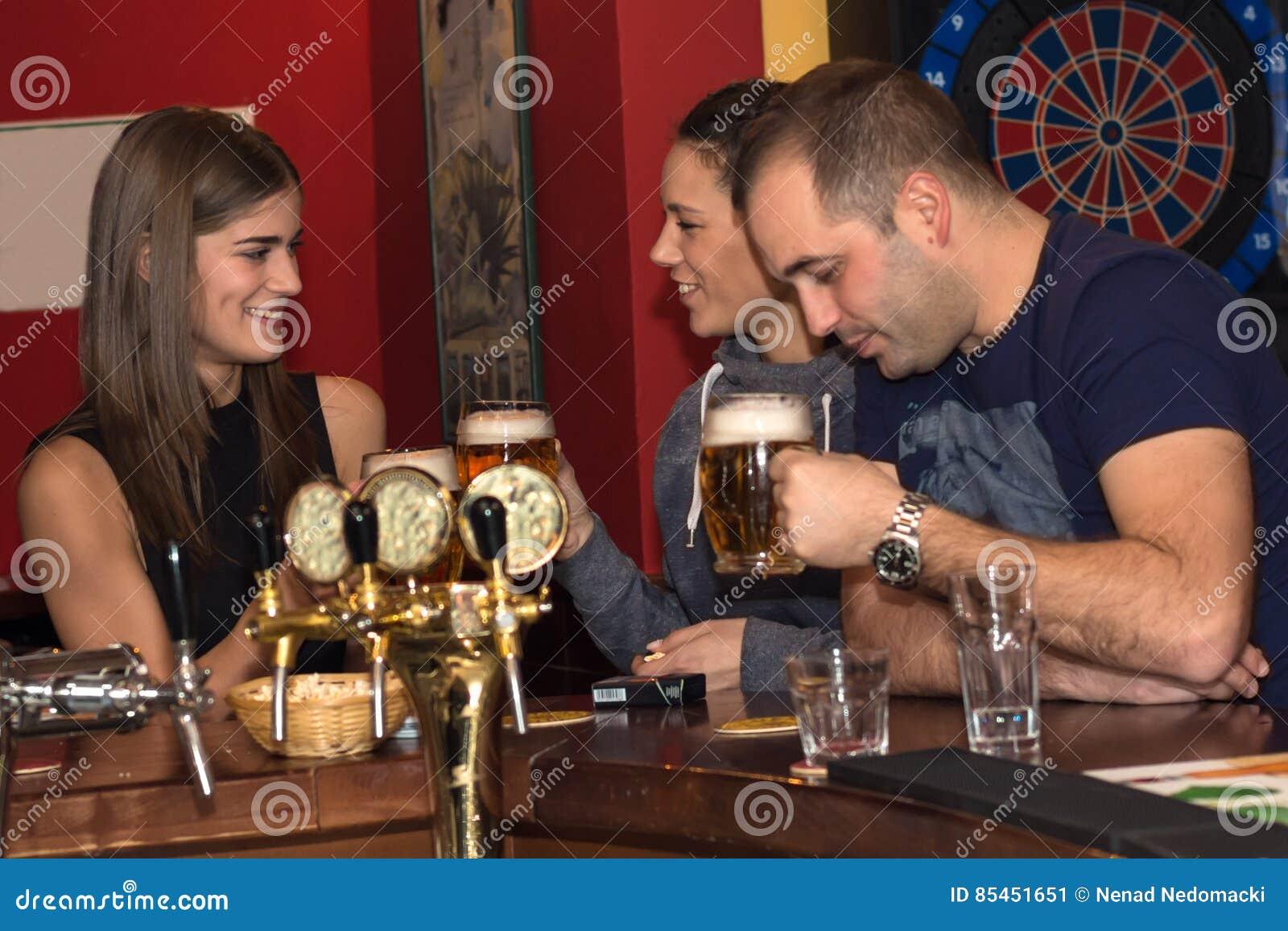 Vänner som har drinkar i en stång