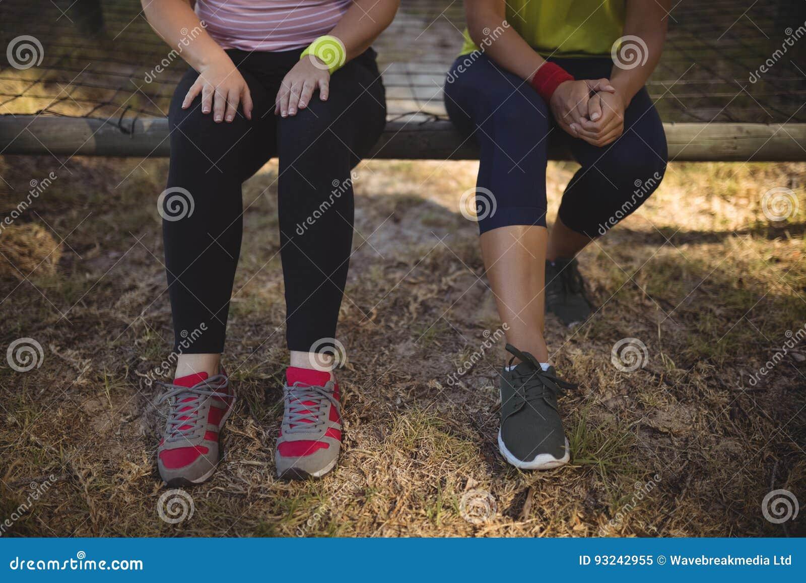Vänner som kopplar av på utomhus- utrustning under hinderkurs