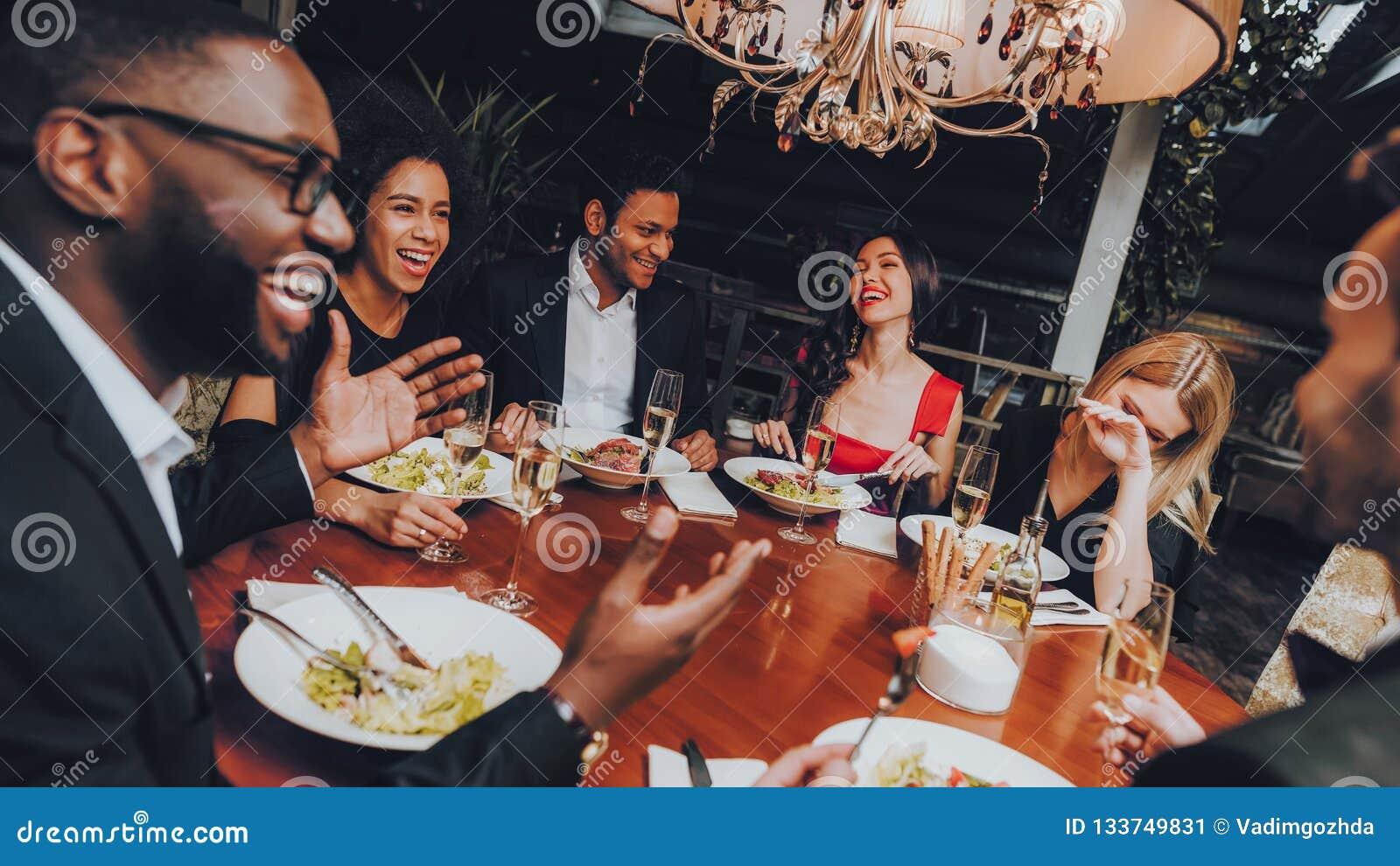 Vänner som kyler ut att tycka om mål i restaurang