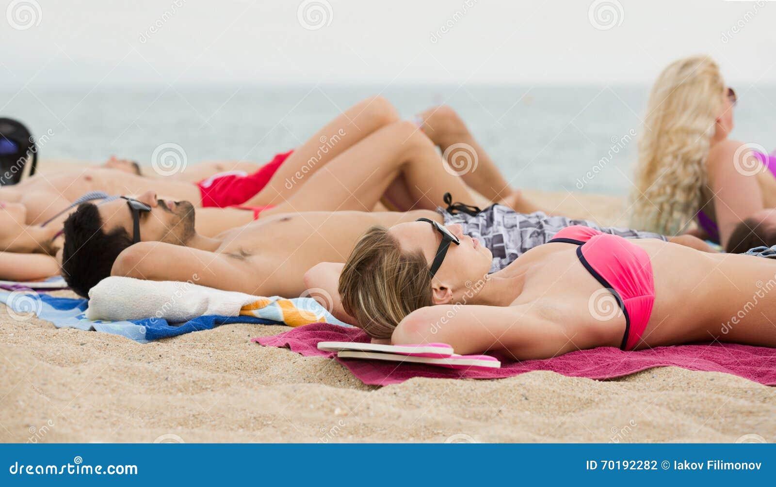 Vänner som lägger på sand på stranden