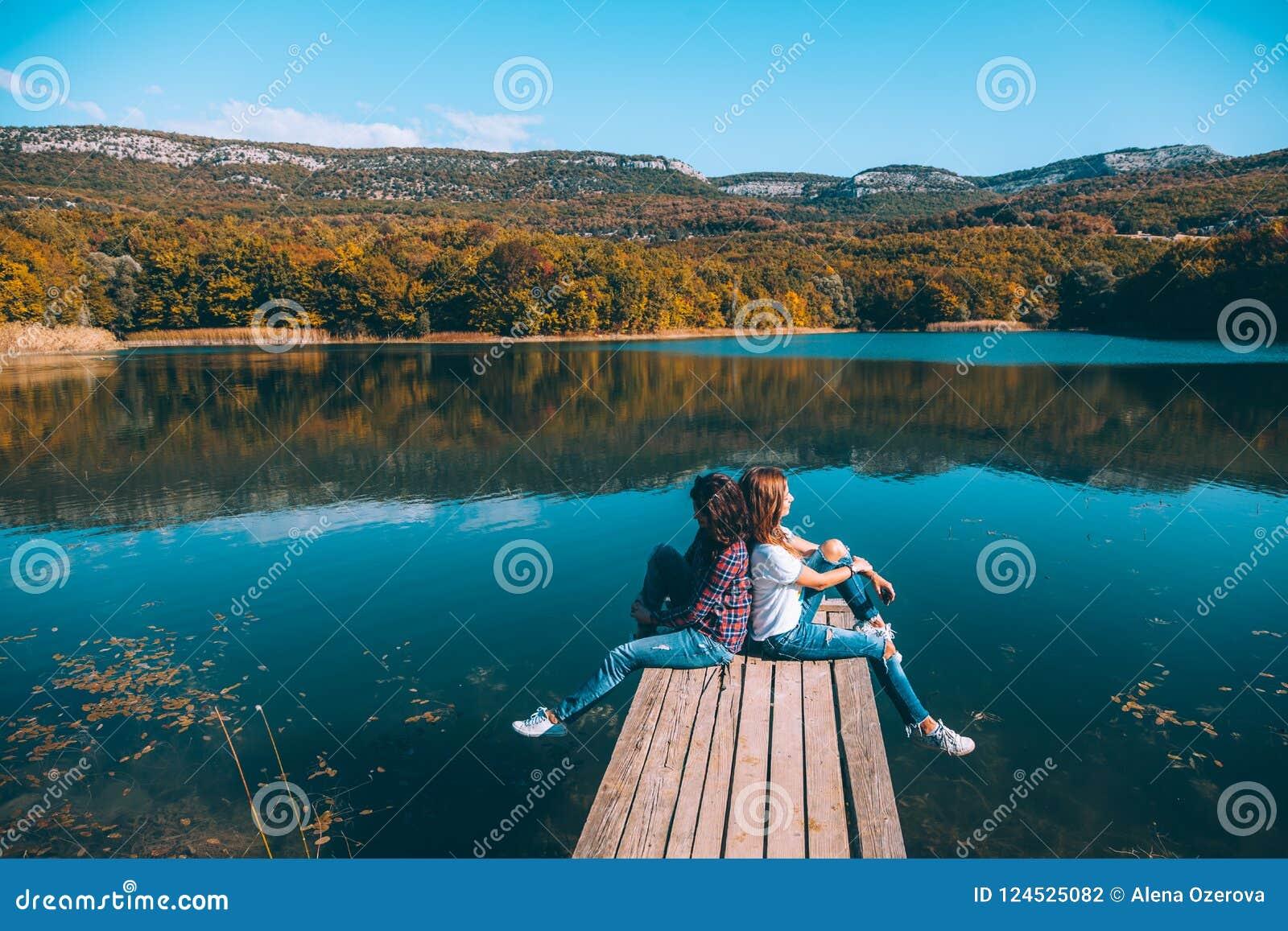Vänner som sitter på jämlike vid sjön