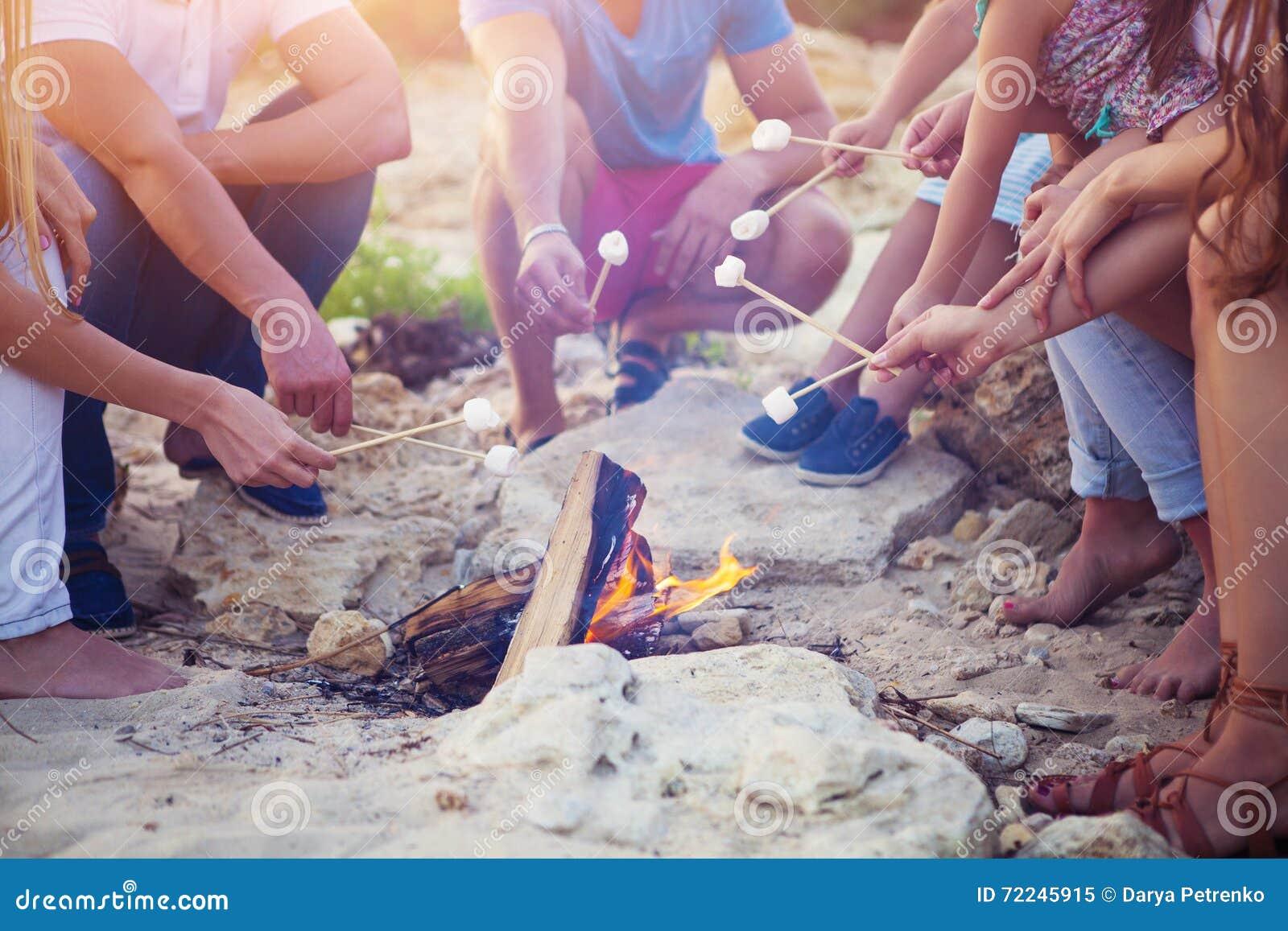 Vänner som sitter på sanden på stranden i cirkel med marshmal