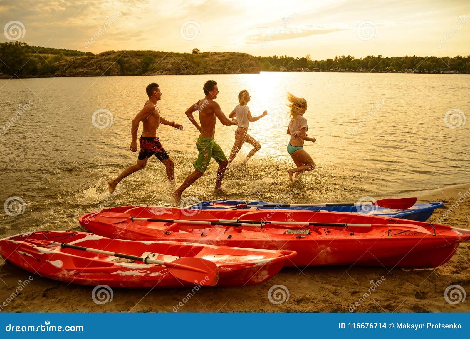 Vänner som spelar och har gyckel i vattnet på stranden nära kajaker under den dramatiska aftonhimlen på solnedgången