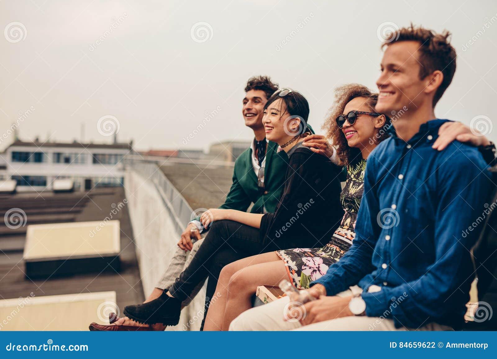 Vänner som tillsammans sitter på tak