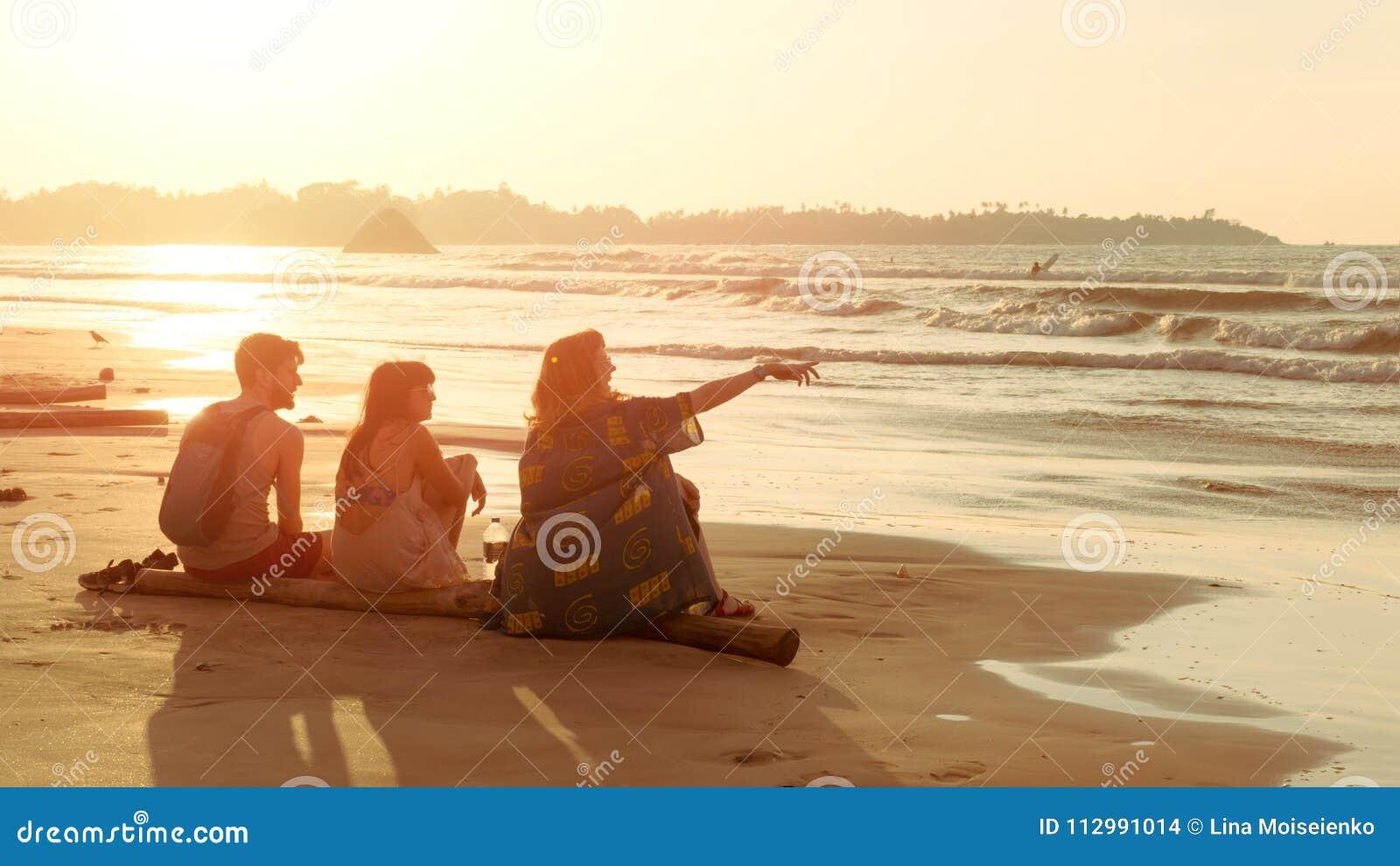 Vänner två unga kvinnor och mannen sitter på den tropiska sjösidastranden på solnedgången och ser vatten Sommartur, semester