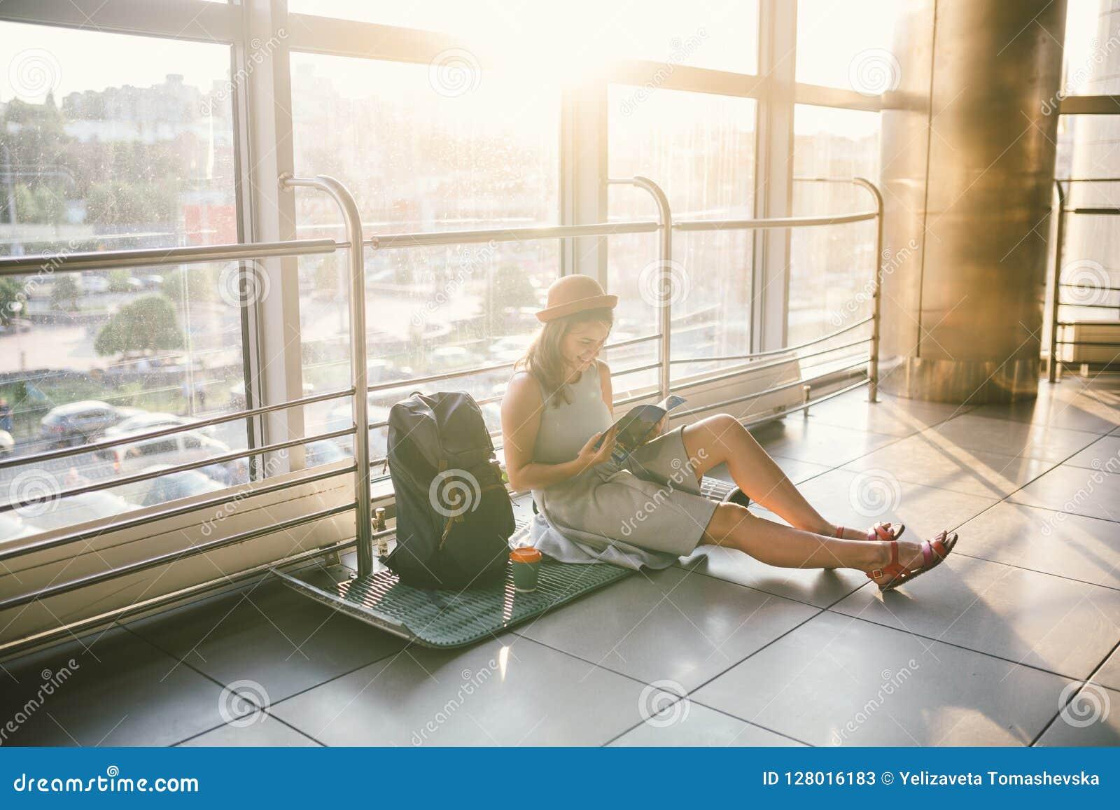 Vänta, försenad transport i terminalen av flygplatsen eller drevstation Den unga caucasian kvinnan i klänning och hatt sitter på