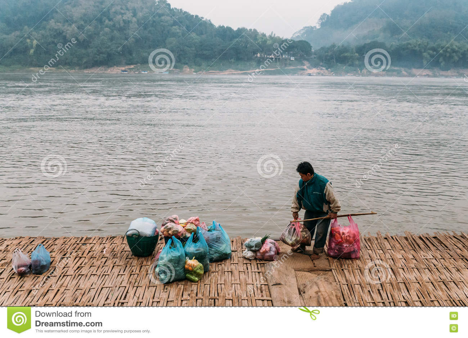 Väntande fartyg för man för rörande artiklar i floden på Luang Prabang, Laos