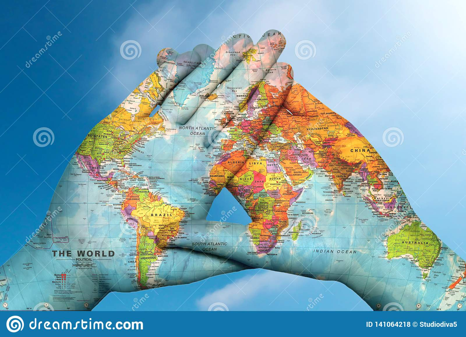 Världskarta i händer mot himlen