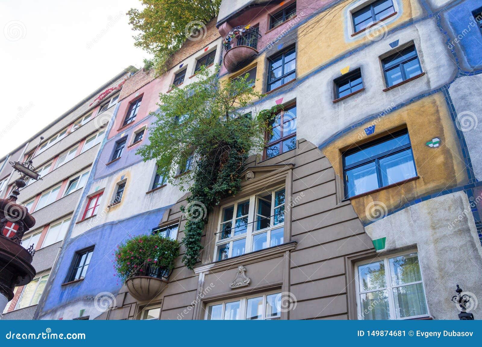 Växande träd från den färgrika väggen av det berömda huset i Wien på hösten