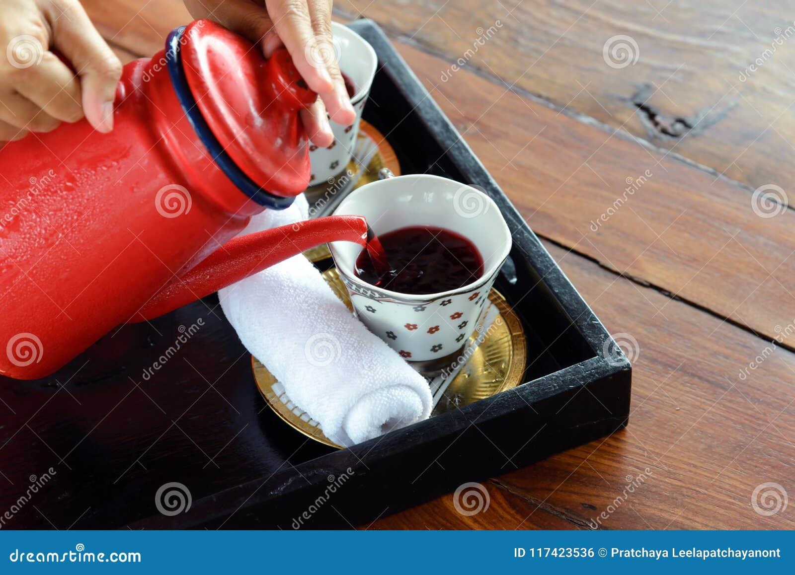 Växt- drinkar som göras från Roselle fruktsaft, lemongrass och söt basilika med kalla handdukar - servitrins häller den välkomna