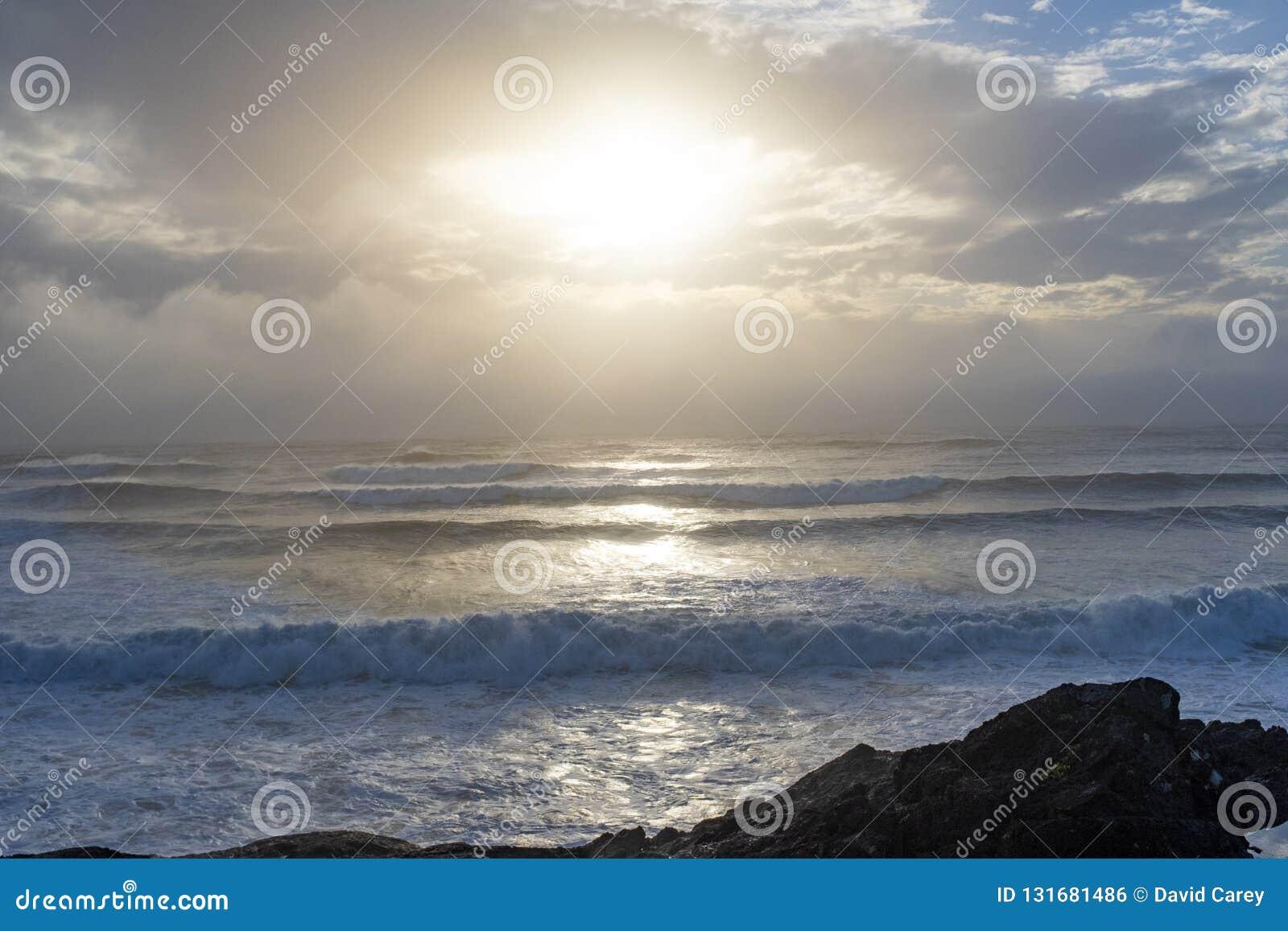 Vågor sköljas upp på stranden på styrmanfjärden i Tofino, F. KR.