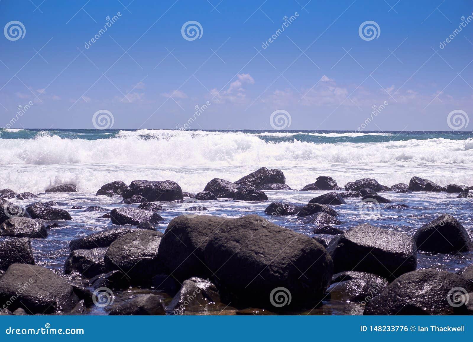 Vågor som bryter över, vaggar på en solig dag