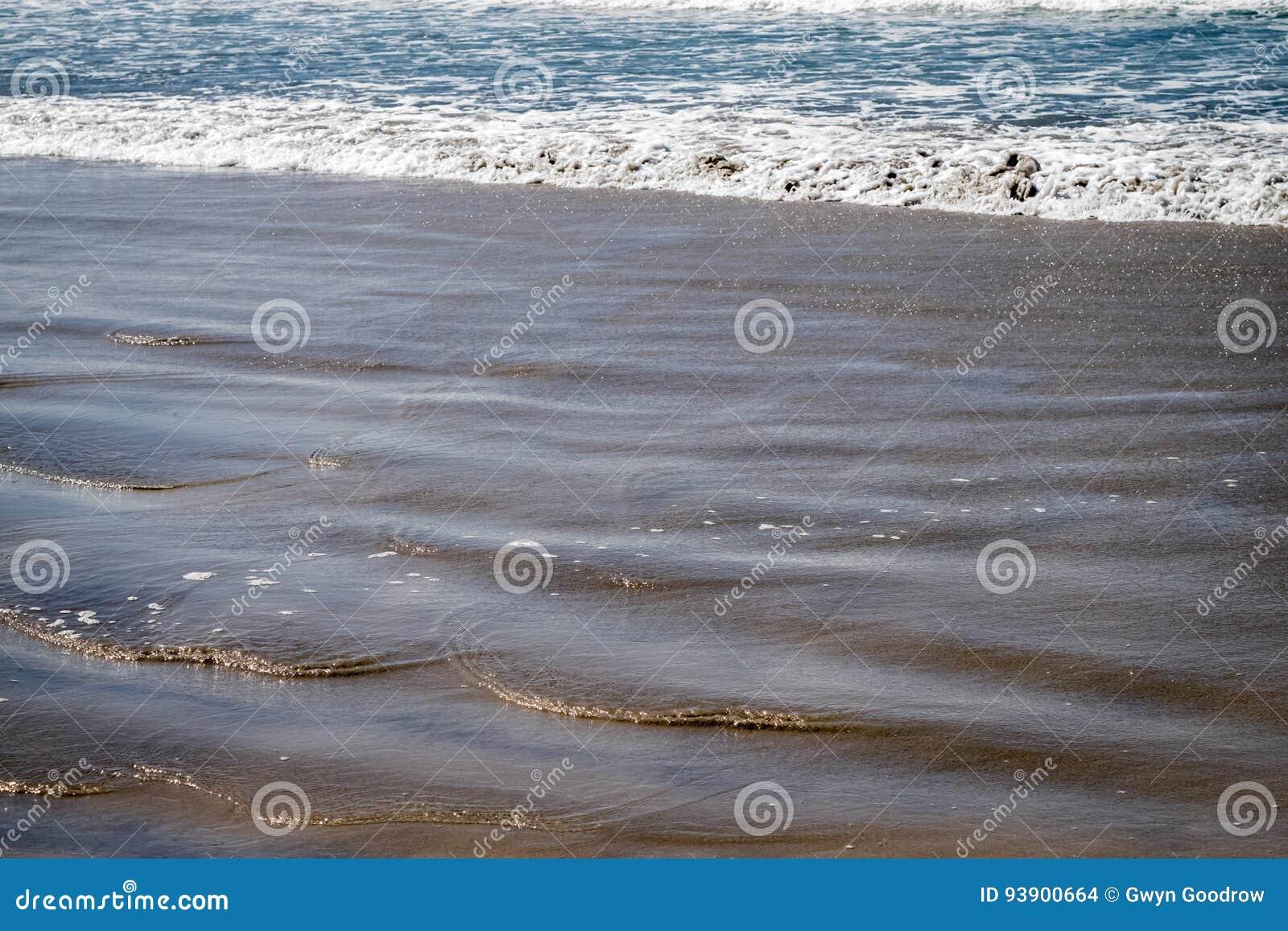 Vågor svaller på den sandiga stranden