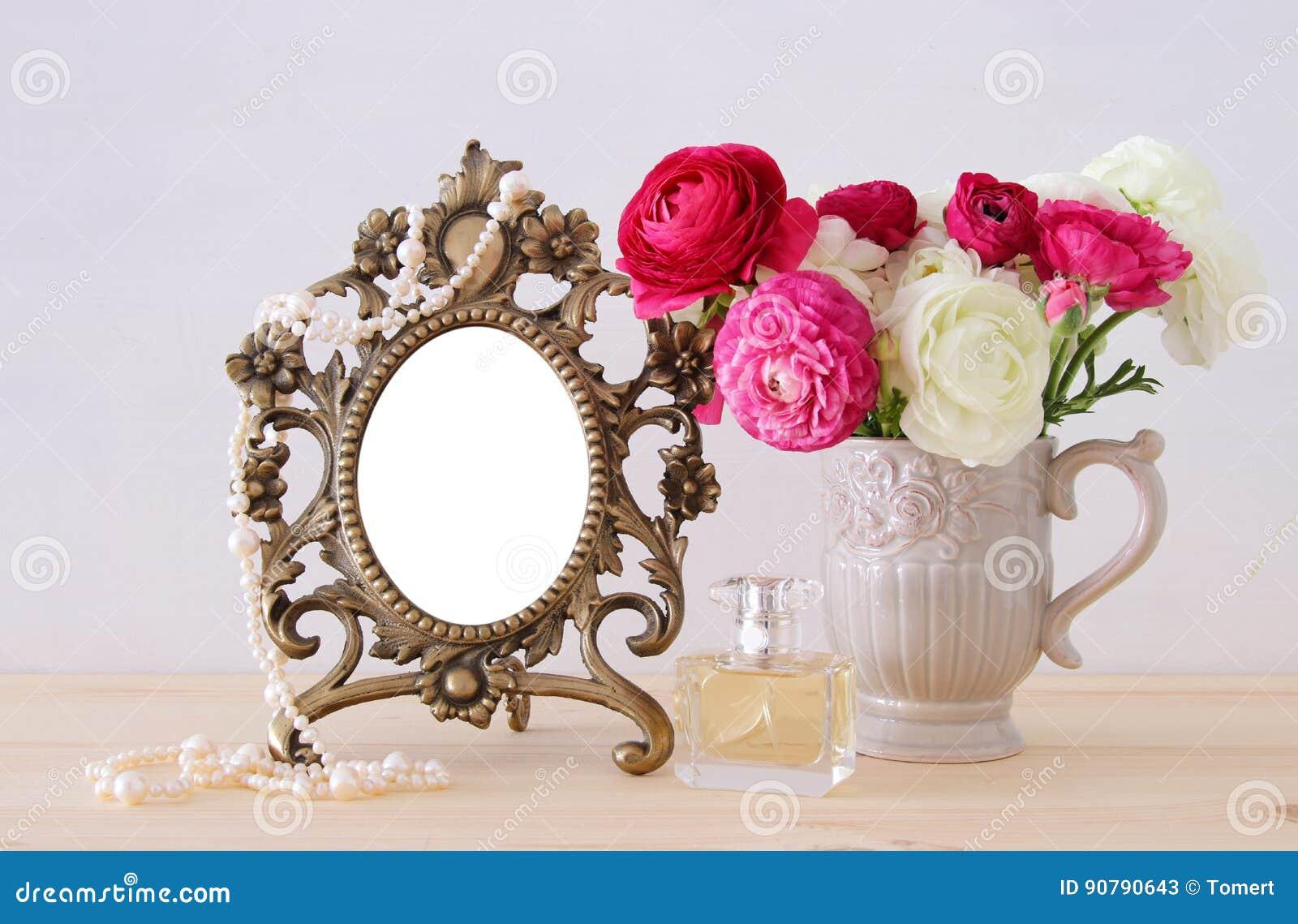 Vårblommor, doftflaska och pärlor bredvid tom tappningfotoram