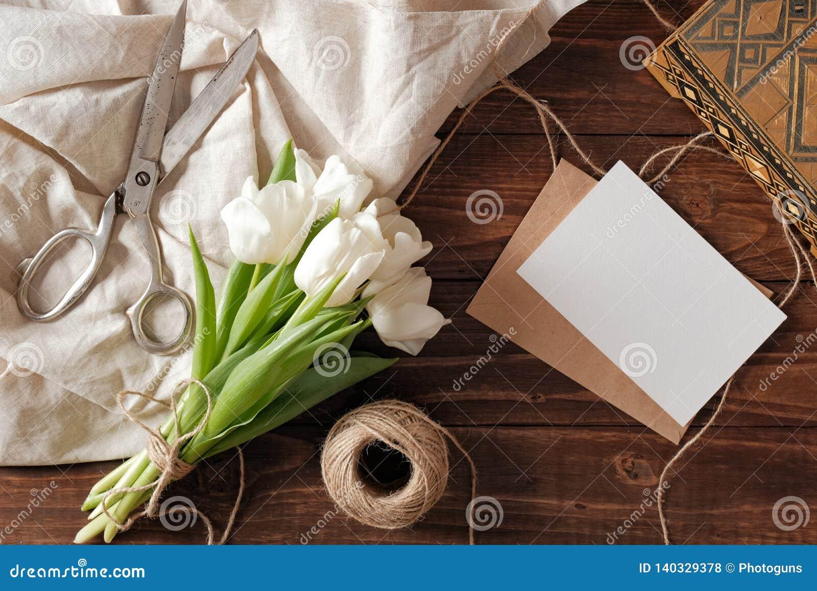 Vårbuketten av vita tulpanblommor, det kraft kuvertet med det tomma kortet, sax, tvinnar på den lantliga trätabellen Composi för