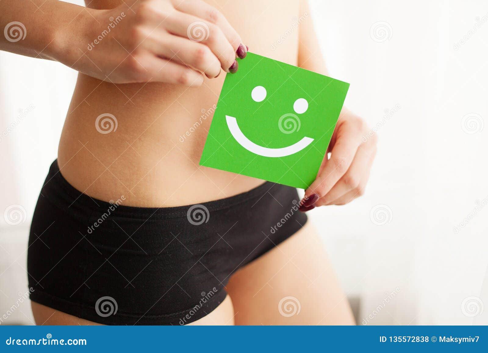 Vård- kvinnor Closeup av den sunda kvinnlign med den härliga färdiga slanka kroppen i svarta underbyxorar som rymmer det gröna ko