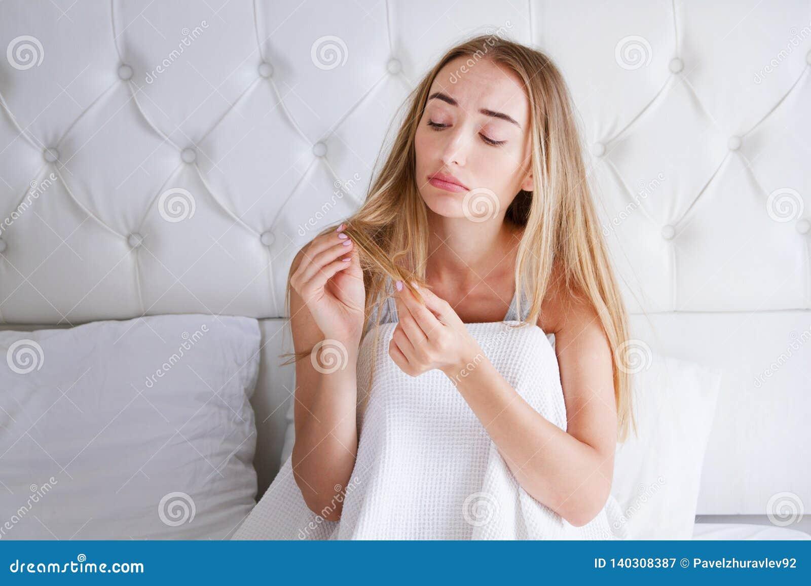 Vård- och skönhet Stående av den härliga ledsna unga kvinnan med långt hår i hand i sovrum Closeup av den olyckliga kvinnliga mod