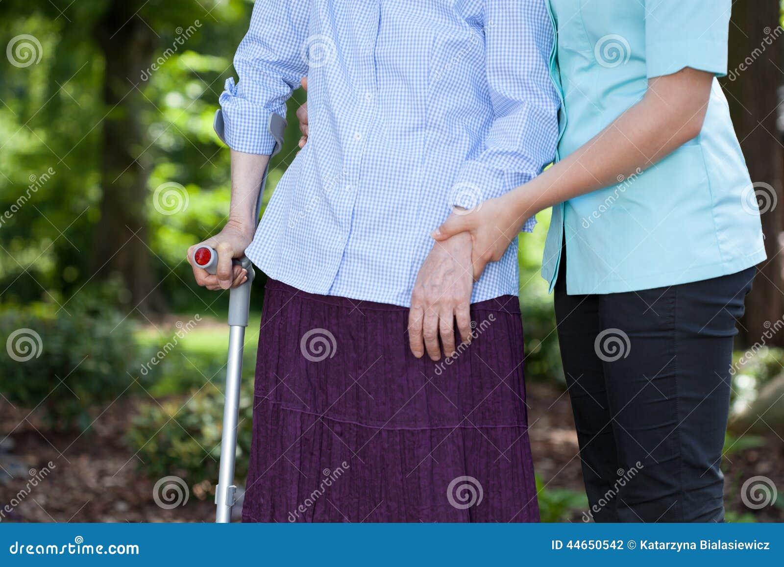 Vårda att gå med en kvinnlig patient med en krycka