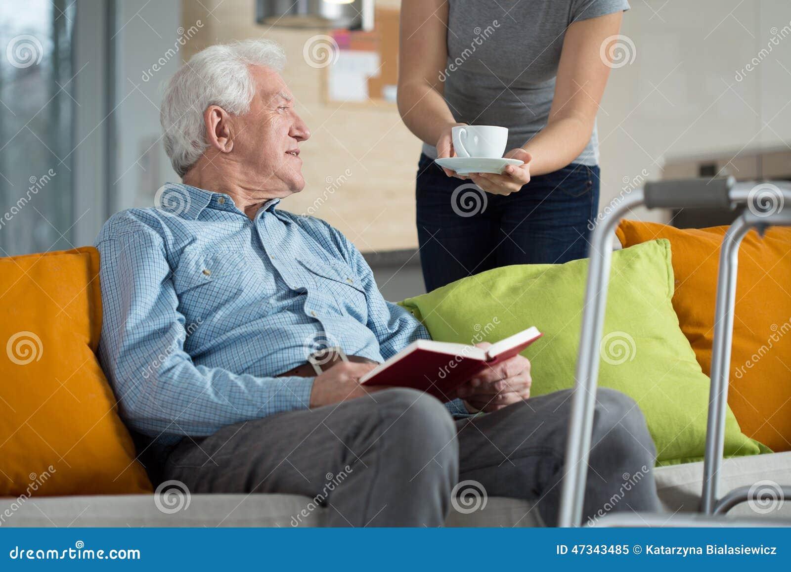 Vårdare som ger rörelsehindrat mankaffe