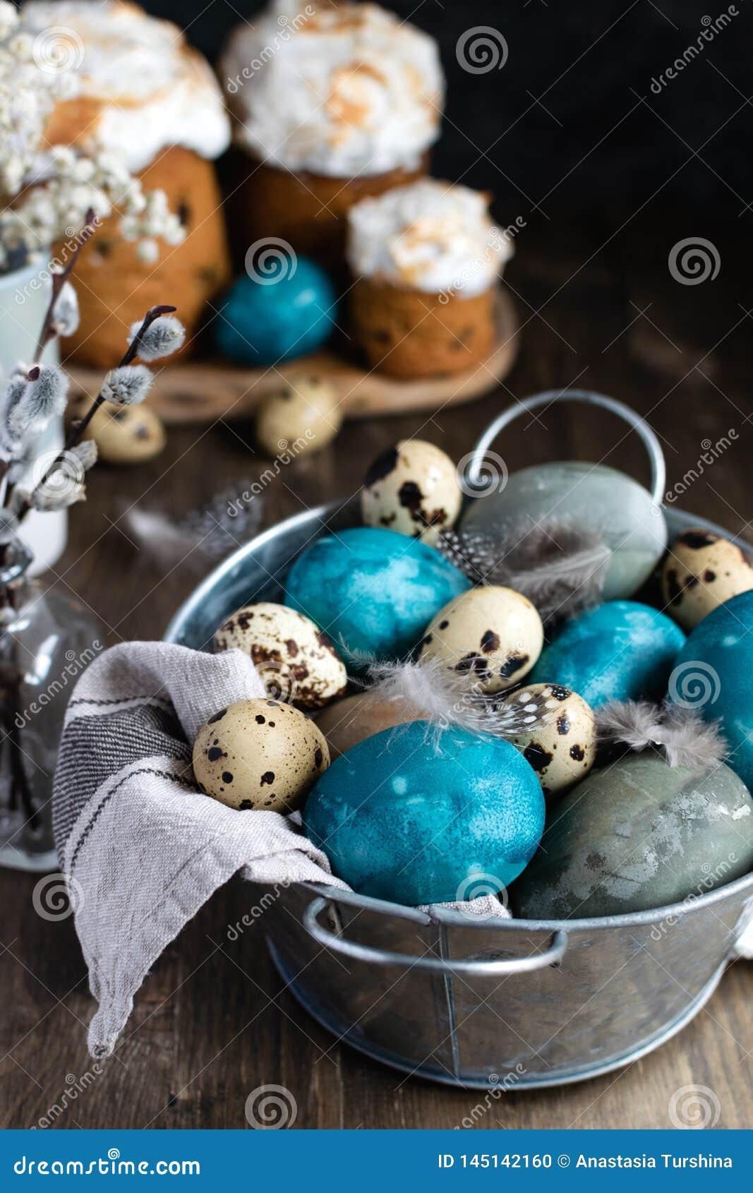 Våreaster begrepp, - färgade naturligt easter ägg, vaktelägg, fjädrar, den easter kakan, mörk träbakgrund, kopieringsutrym