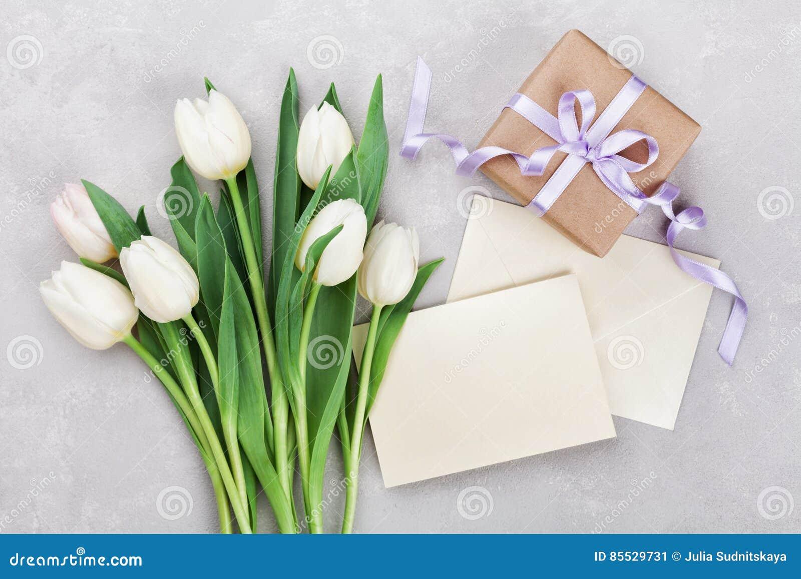Vårtulpan blommar, gåvaasken och det pappers- kortet på grå färgstentabellen från ovannämnt i lekmanna- stil för lägenhet Hälsnin