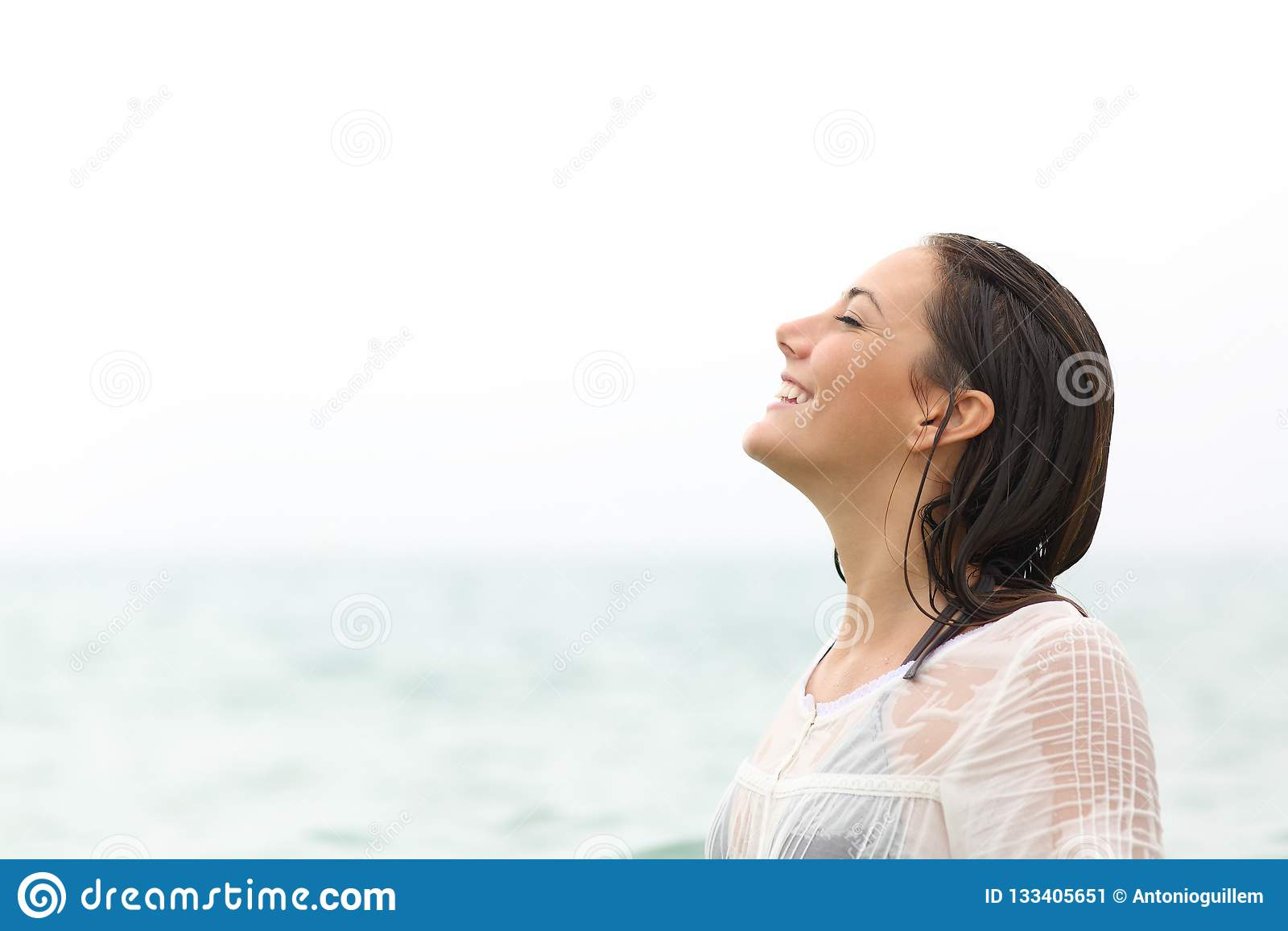 Våt kvinna som andas ny luft på stranden