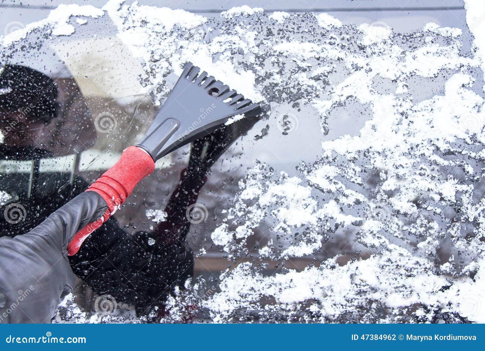 Véhicule sur une route de l hiver La main de l homme érafle la glace et la neige