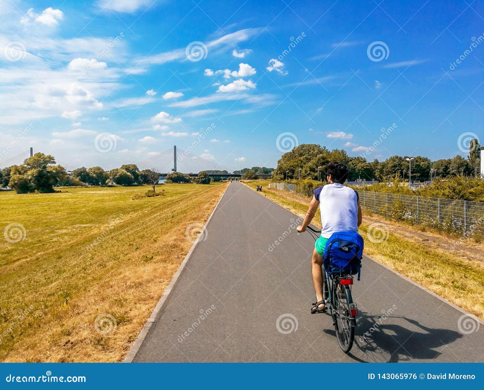 Vélo d équitation d homme au-dessus de ligne de bicyclette dans la fève, Allemagne