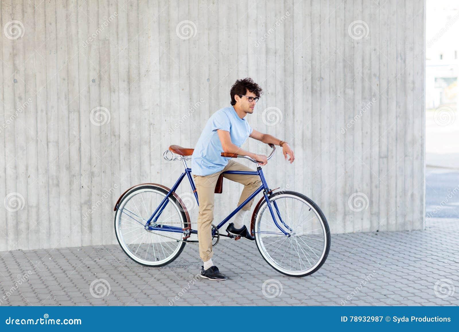 Vélo fixe de monte de vitesse de jeune homme de hippie