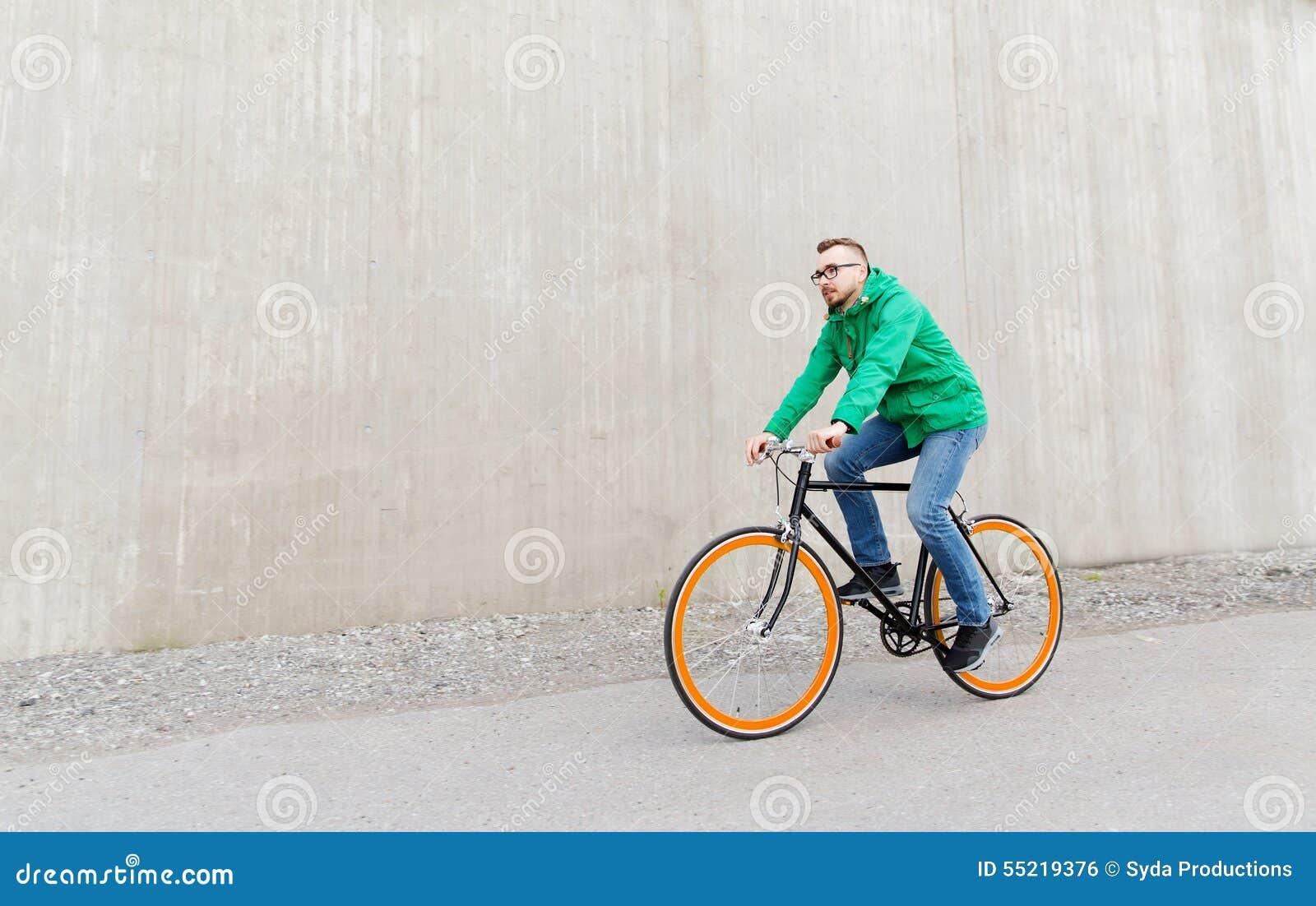 Vélo fixe de monte de vitesse de jeune homme heureux de hippie