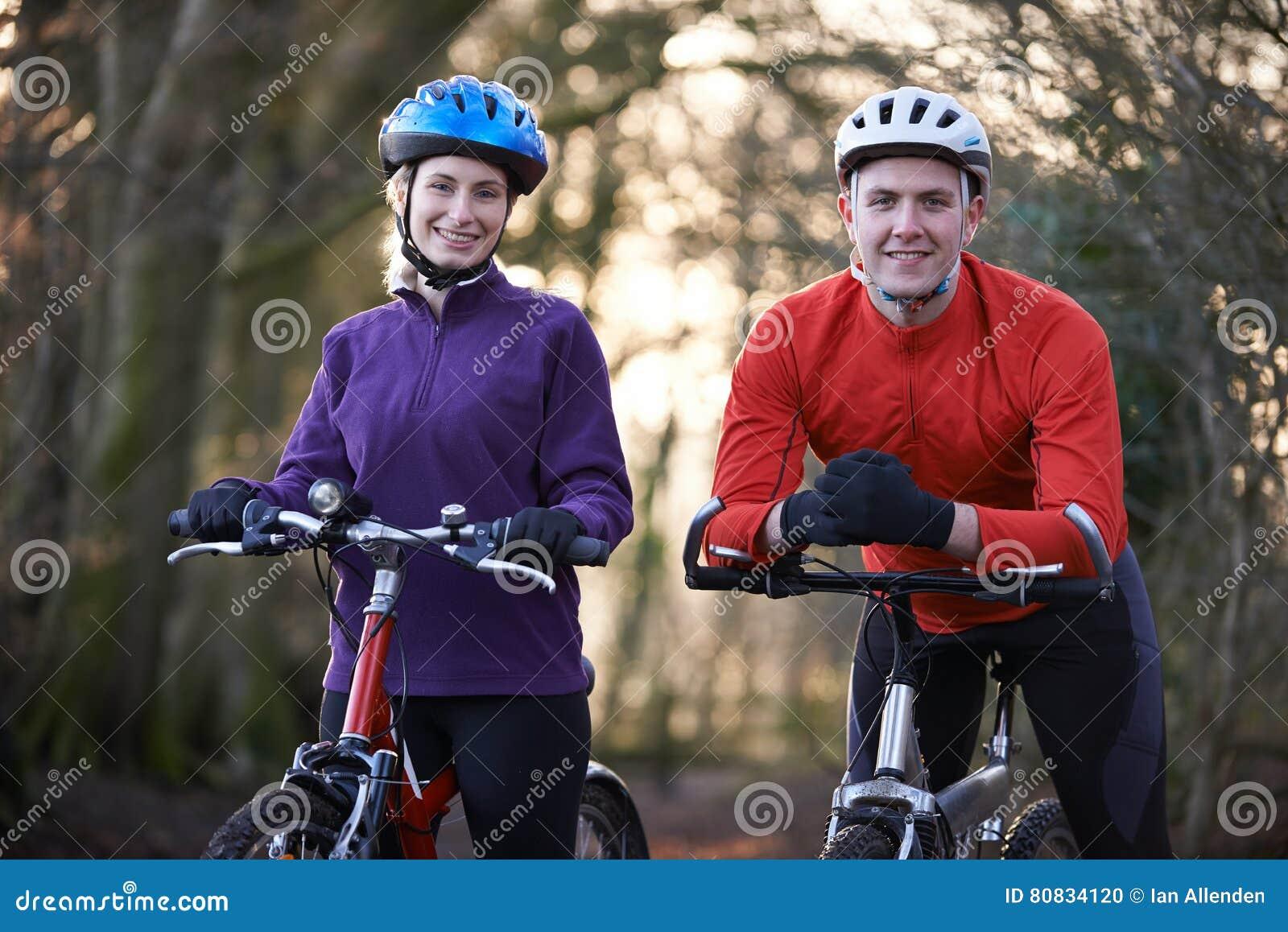Vélos de montagne d équitation de couples par des régions boisées