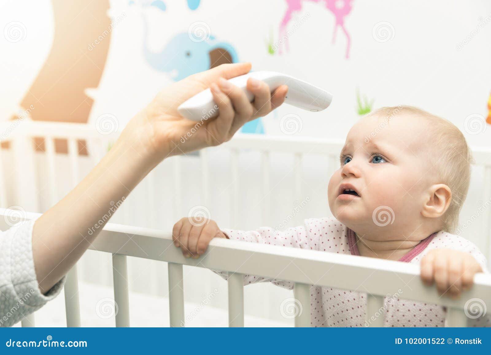 Vérifiez la température du bébé avec non le thermomètre de contact