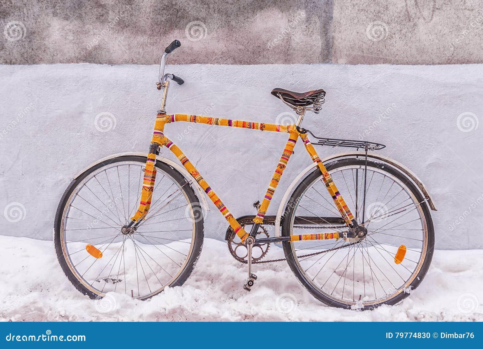 Vêtement tricoté isolé par vélo décoré sur une rue neigeuse