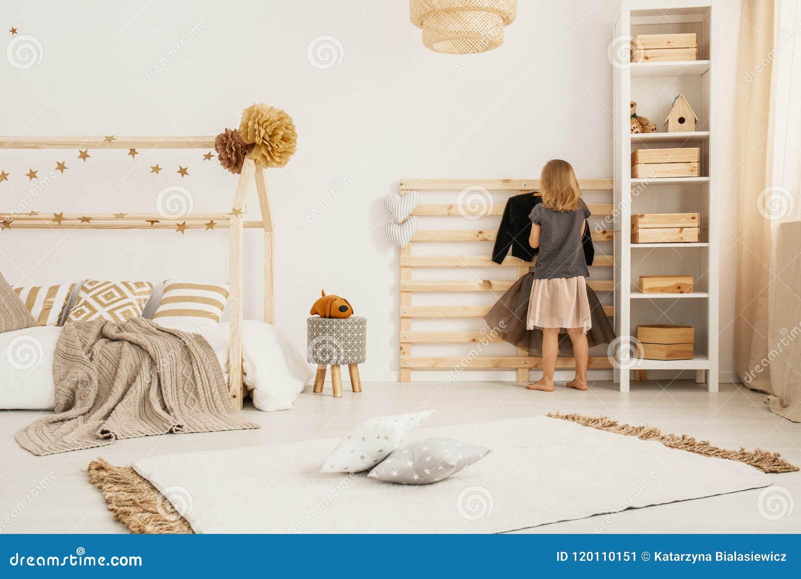 Vêtements accrochants de jeune fille sur le cintre en bois dans le styl nordique blanc