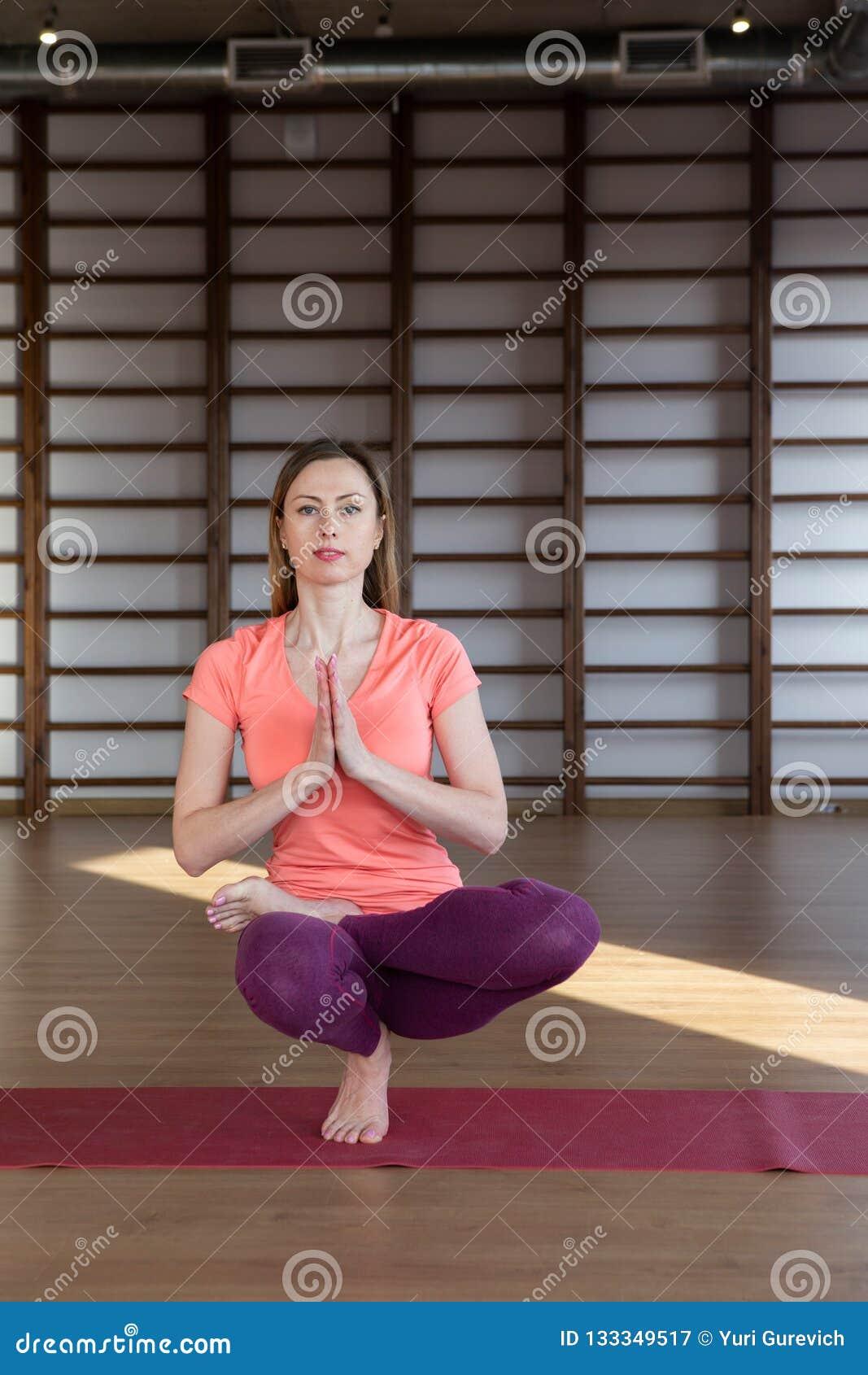 Vêtements de sport blancs de port de jeune jolie femme calme établissant, faisant l exercice de yoga ou de pilates D isolement su