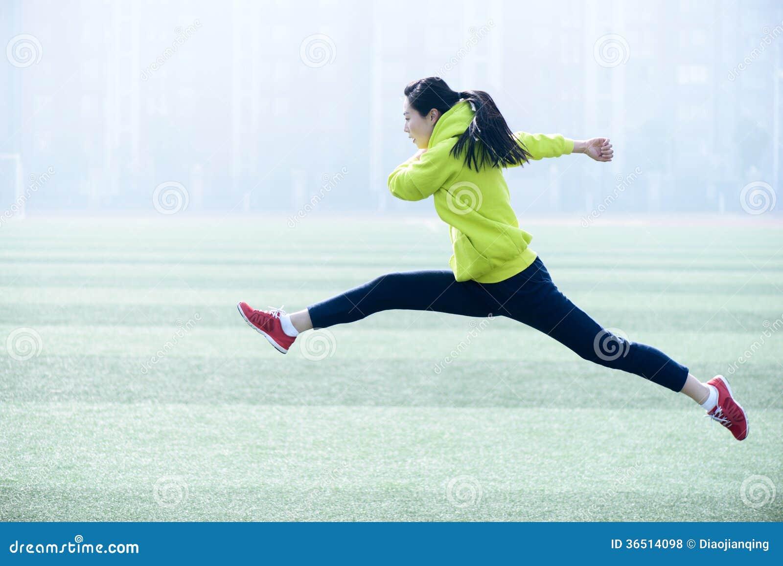Vêtements de sport verts de port sautants de jolie jeune femme.