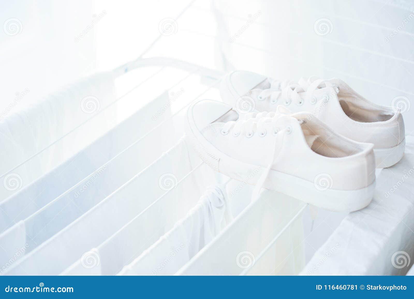 Vêtements et linge de lit blancs dans le dessiccateur