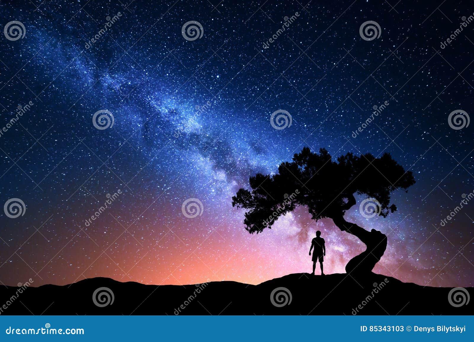 Vía láctea, árbol y silueta del hombre solo Paisaje de la noche