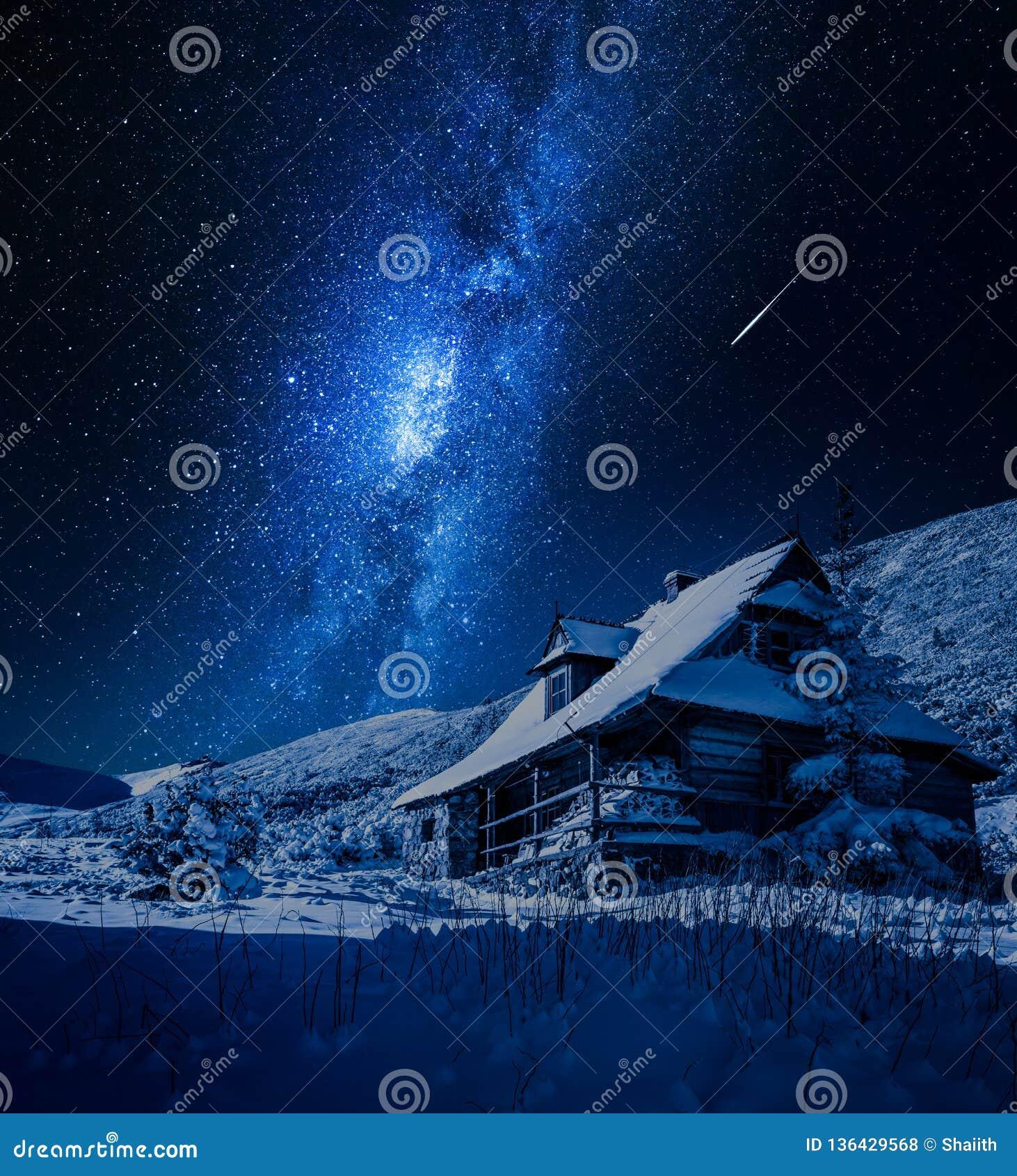 Vía láctea sobre la cabaña de madera en invierno, Polonia de la montaña