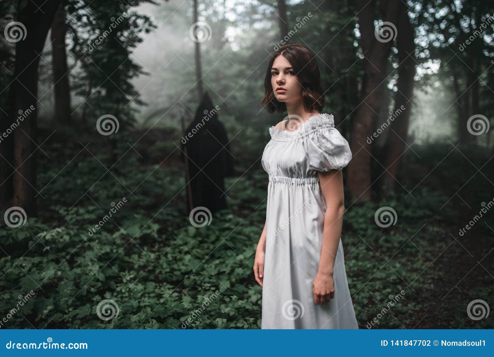 Víctima femenina y muerte en sudadera con capucha negra en bosque