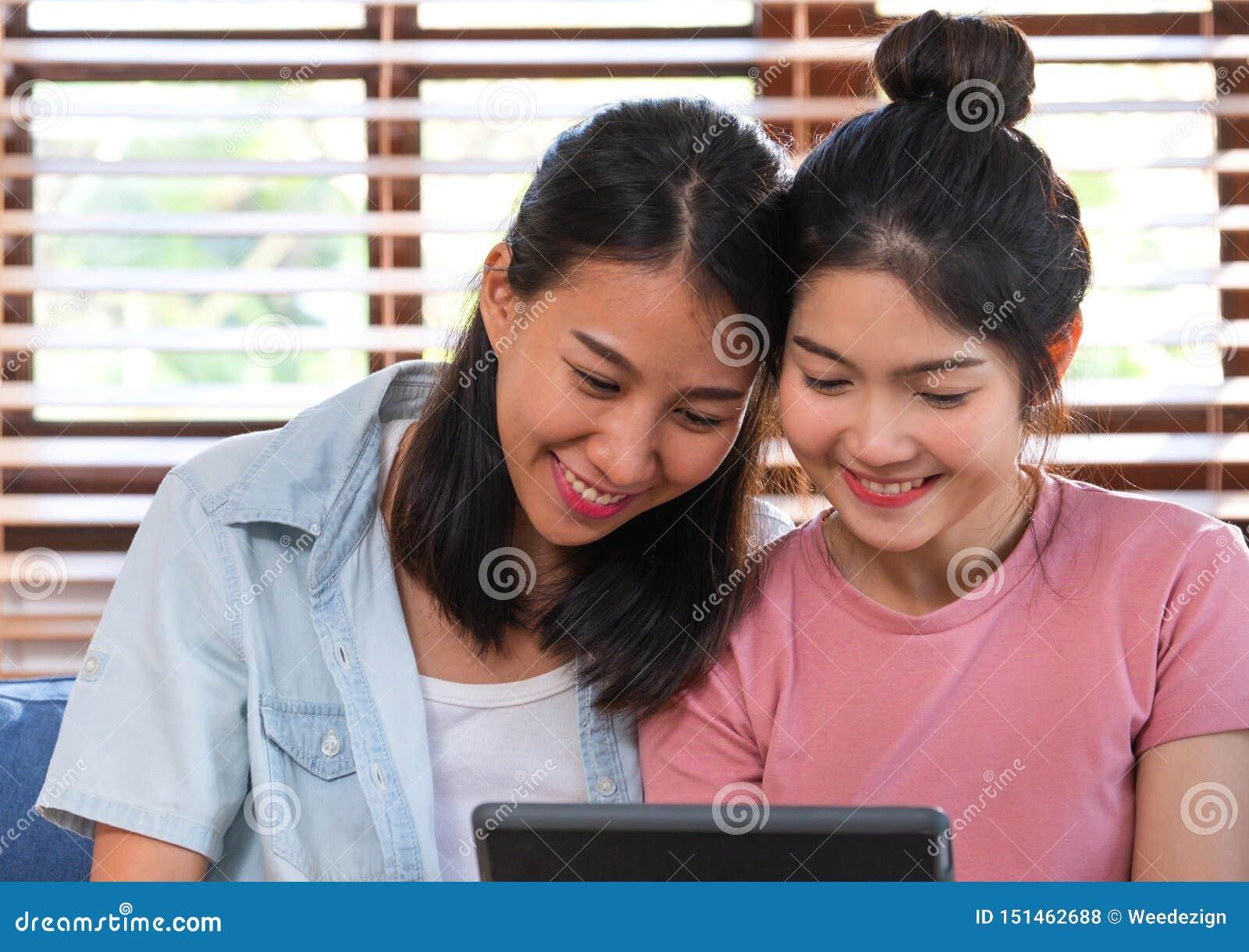 Vídeo de observación de la lesbiana asiática feliz en la tableta en el sofá en casa Concepto de la forma de vida de LGBTQ