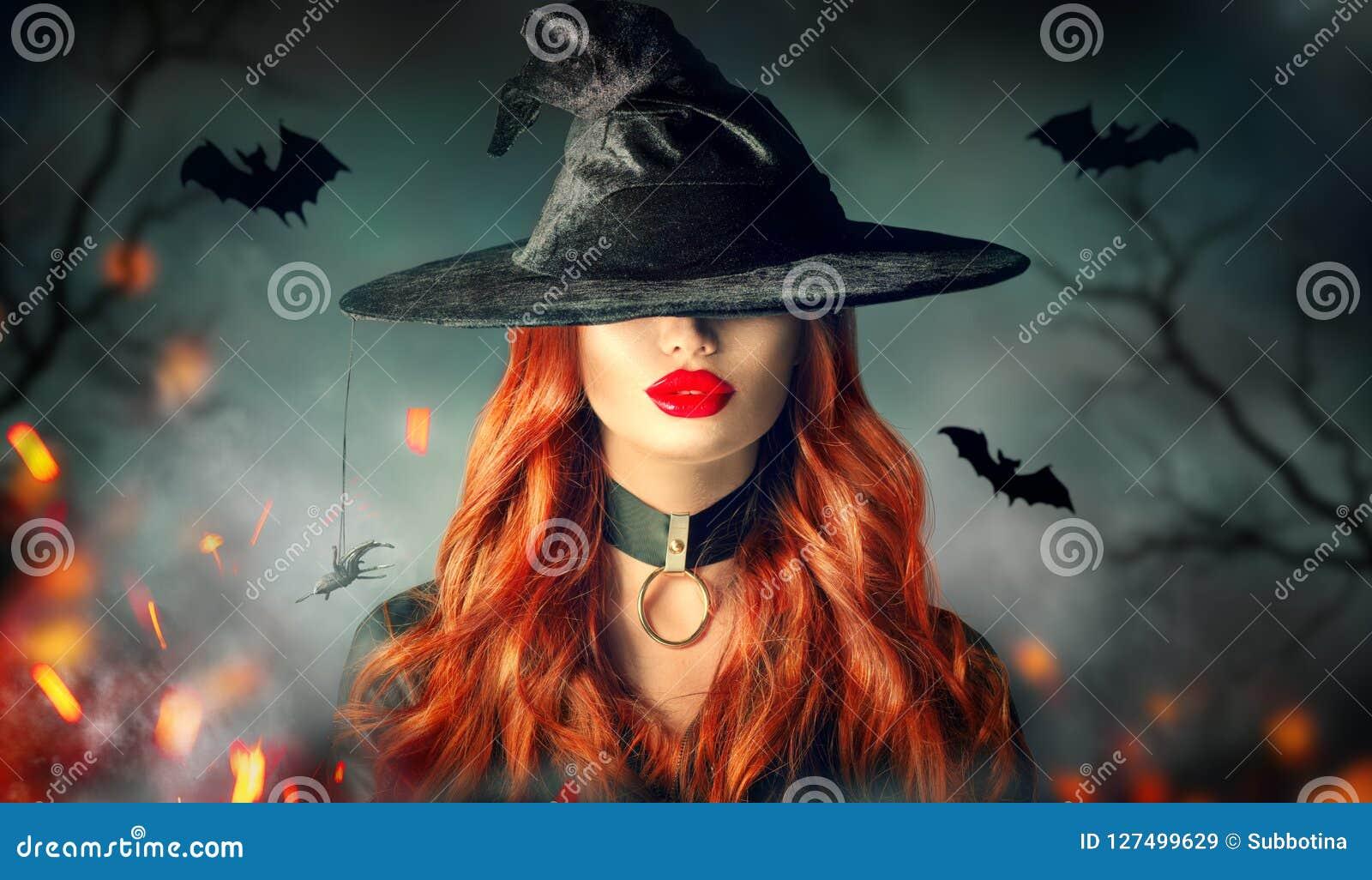 Víspera de Todos los Santos Retrato atractivo de la bruja Mujer hermosa en sombrero de las brujas con el pelo rojo rizado largo