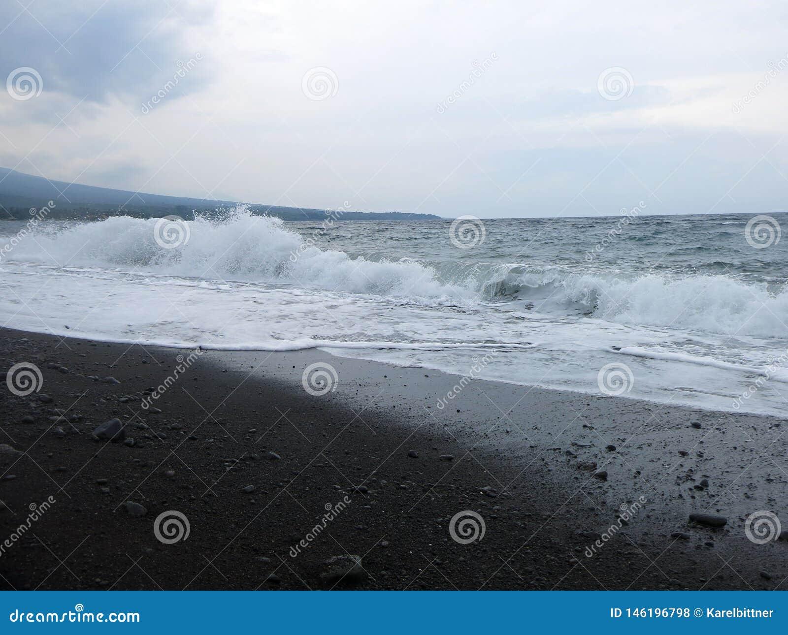 V?g-, br?nning- och havsskum som sl?r den sandiga svarta vulkaniska sandstranden av Bali I Amed ?r havet tyst, men v?gorna runt o