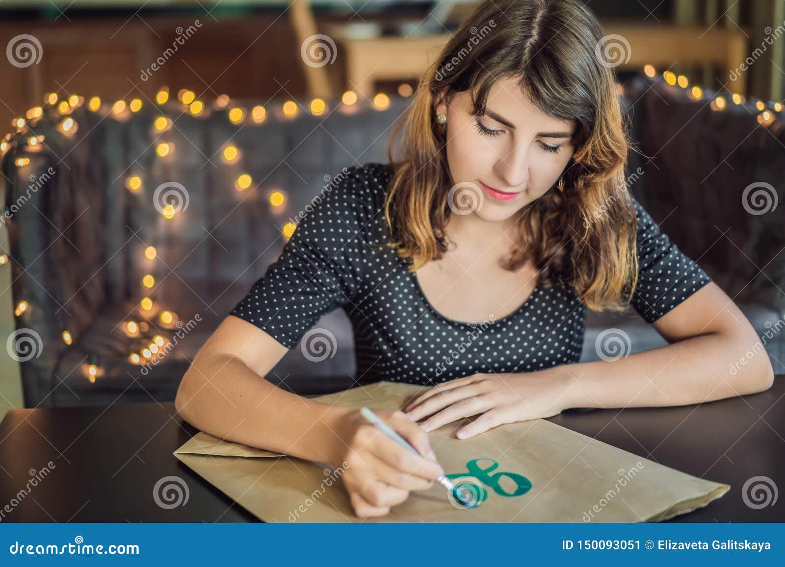 Va il verde Il calligrafo Young Woman scrive la frase su Libro Bianco Iscrivendo l ornamentale ha decorato le lettere calligraphy