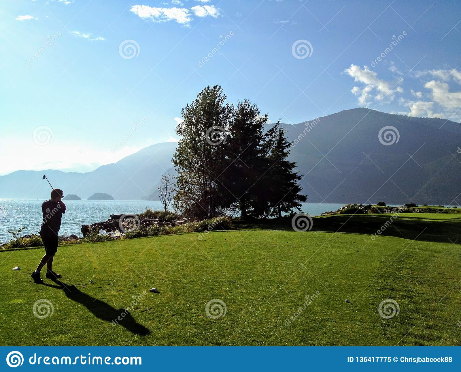 VA man playing golf along the ocean in howe sound, British Columbia, Canada. It is a beautiful sunny day.