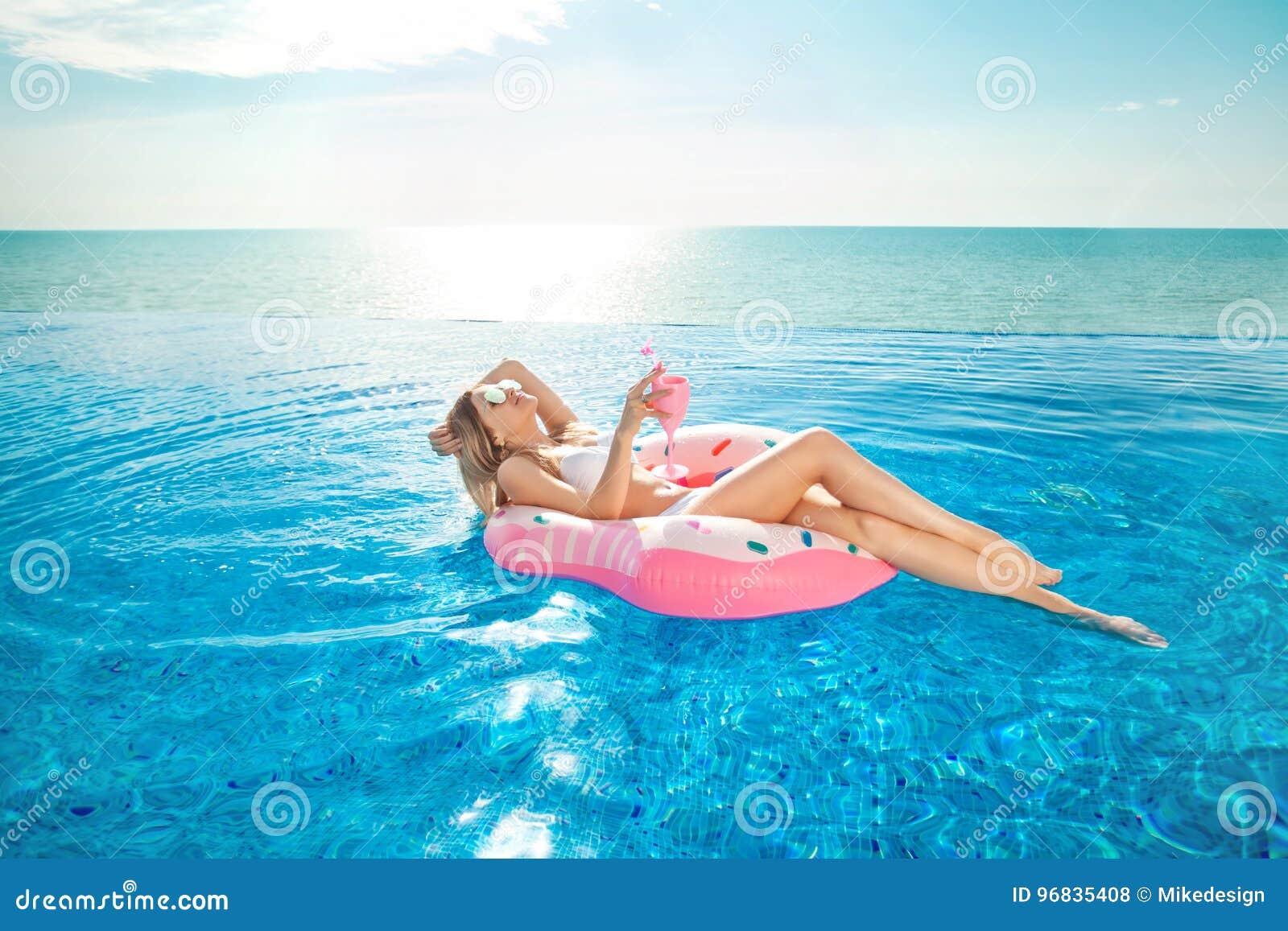 Vacaciones de verano Mujer en bikini en el colchón inflable del buñuelo en la piscina del BALNEARIO