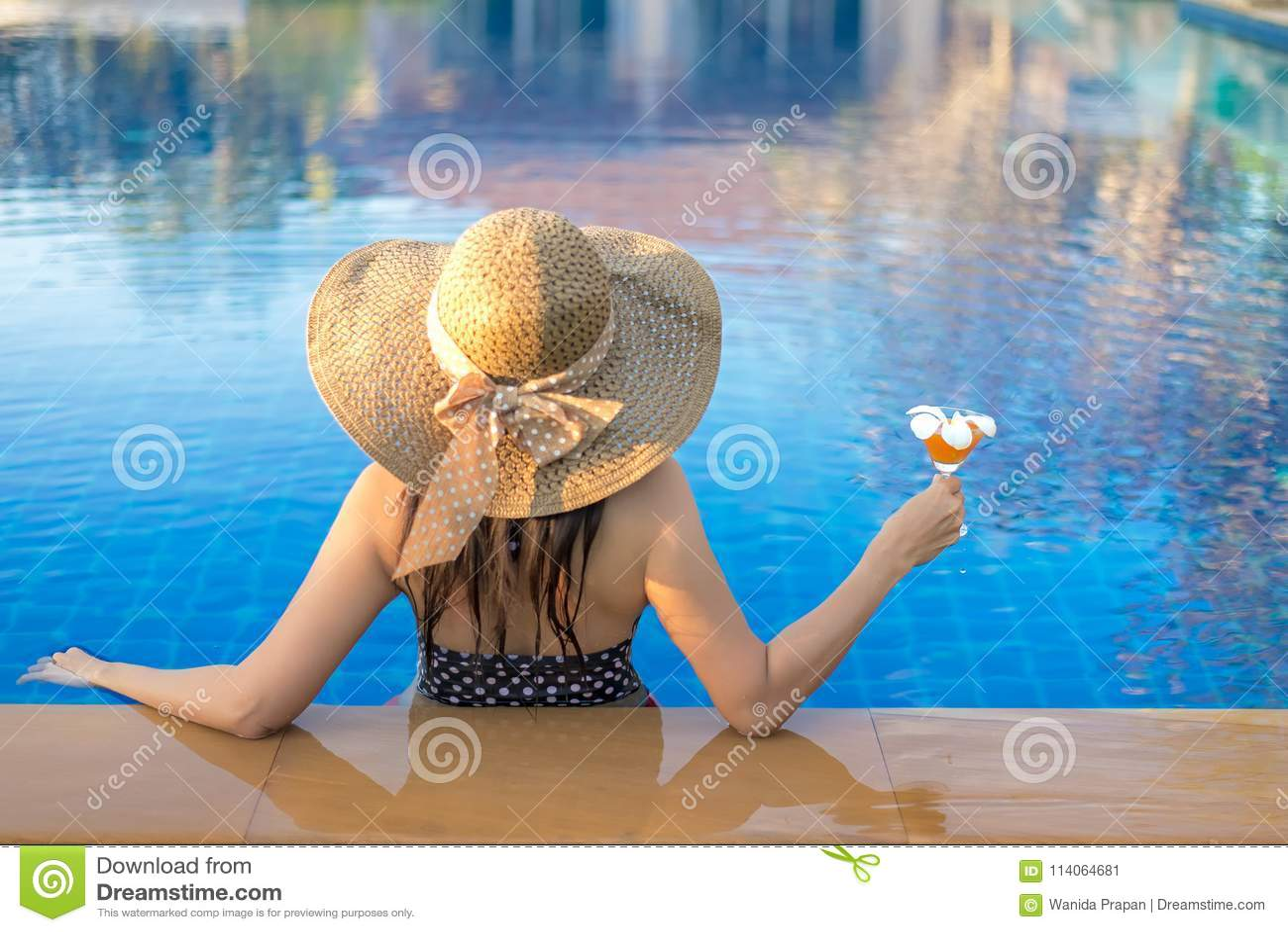 Vacaciones de verano Mujer de la forma de vida feliz con el bikini y el sombrero grande que se relajan en la piscina, en día de f