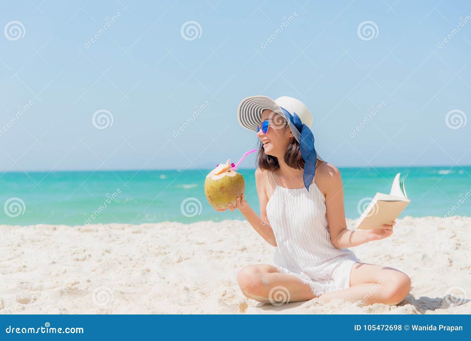 Vacaciones de verano Mujeres asiáticas que huelen que se relajan, libro de lectura y cóctel de consumición del coco en la playa,